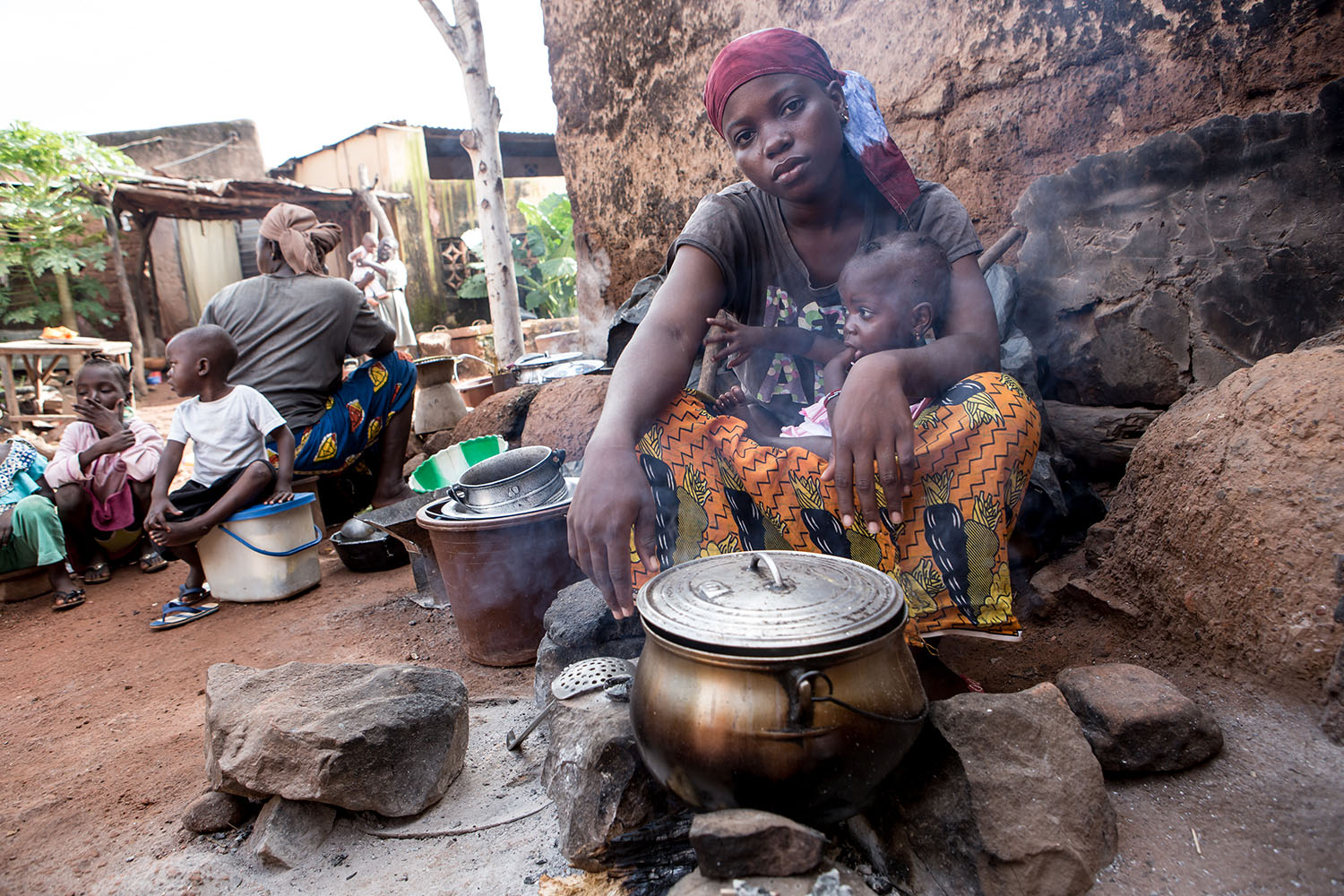 "Awa prepares a meal for the family at their homestead. ""Although Sikasso is seemingly the bread basket of Mali, the rate of malnutrition here remains surprisingly high. This can be attributed to mothers refusing to breastfeed properly, an inability to t"