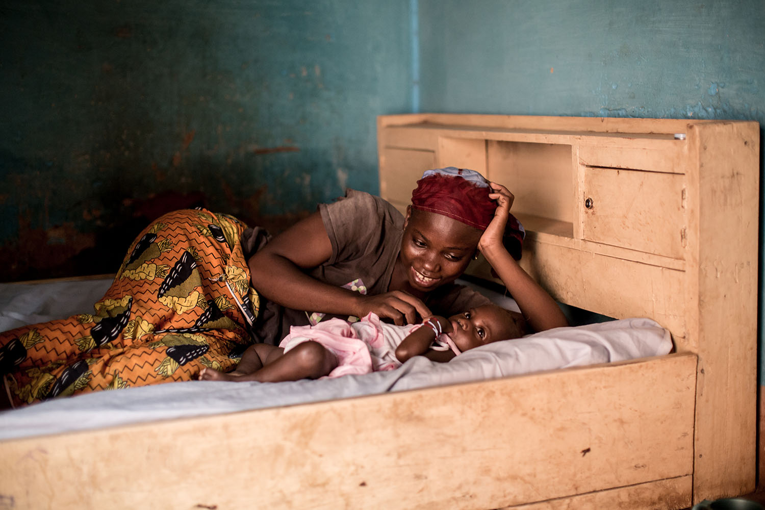 "Awa (20 yrs) and Nantene (18 months) enjoy a moment together on their bed at home. But a few months ago Awa, almost lost her first and only child to chronic acute malnutrition. Thanks to UNICEF and the distribution of ""Plumpy Nut"" a peanut based prduct us"