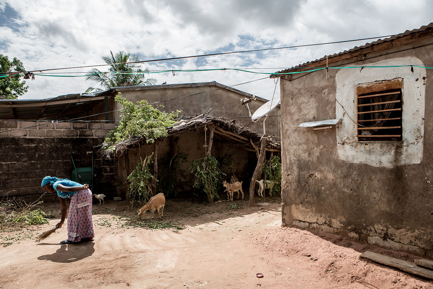 """Waraba Doumbia, 16 years (released) sweeps the family's homestead, one of many chores she is expected to complete during her day. """"When I get up in the morning and watch my brothers and sisters getting ready for school, I feel very sad that I no longe"""