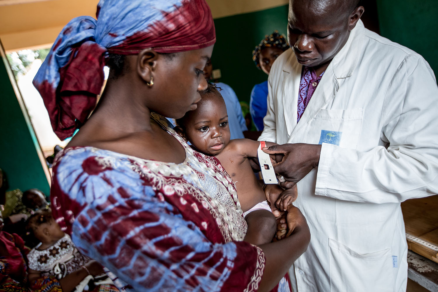 Awa and Nantene at the CScom Wayerma1 Health Centre, SIkasso  where the doctor checks Nantene's MUAC (measurement upper arm circumference) UNICEF continues to emphasise prevention activities and increasing access to quality care for severely malnourishe