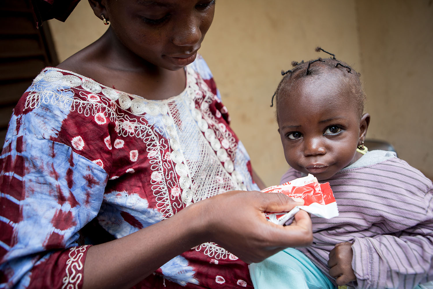 "Awa and Nantene receive a sachet of ""plumpy Nut"" which is a peanut-based paste administered for the treatment of severe acute malnutrition. UNICEF continues to emphasise prevention activities and increasing access to quality care for severely malnour"