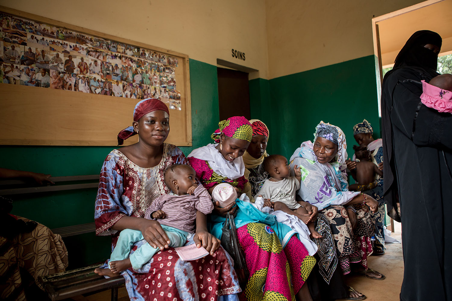 Women wait at the local clinic where their babies are examined, inoculated and cared for. Although Plumpy Nut is a major contributor to reducing the rate of malnutrition in the region, a behavioural change amongst the community is also necessary. Women'