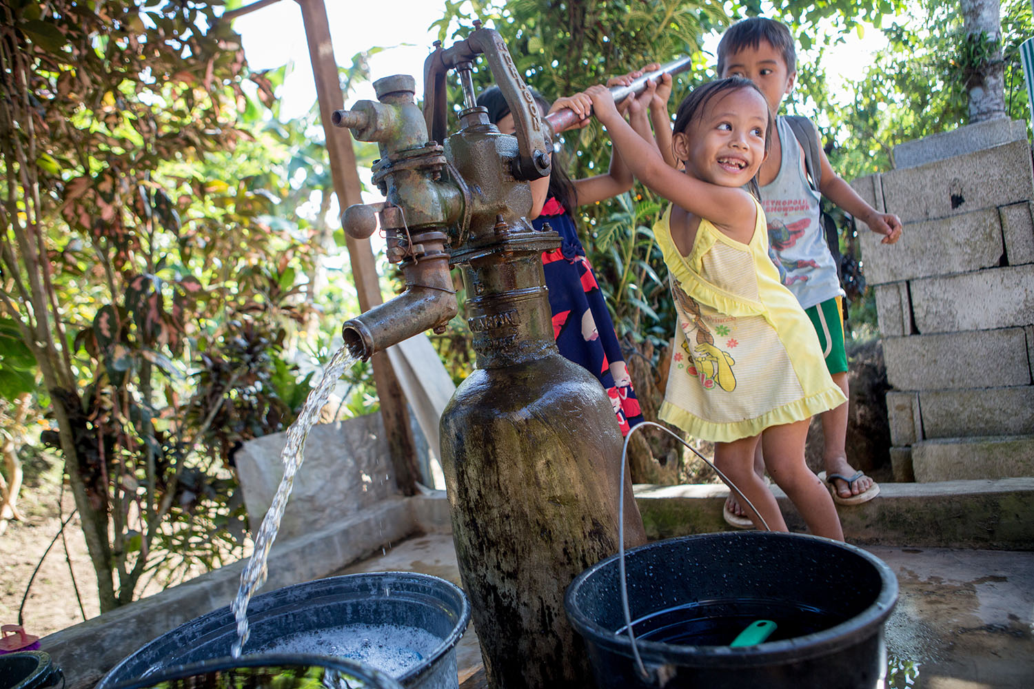 Alvin Johnson Raga, Christel Jade Gabiana, Shiane Ariese at the pump during the WASH community visi UNICEF trip to Tacloban, in the Philipines to report on their response to Typhoon Yolanda, March 2016