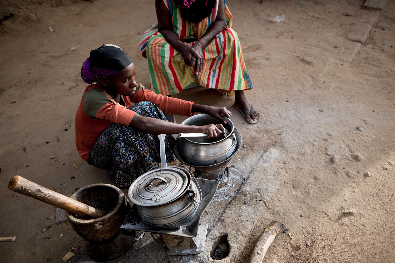 Adeoula, 12 years, (RELEASED) cleans the pots and helps her grandmother do chores at their homestead in the city of Gao, northern Mali. Adeoula and her brother were orphaned during the conflict and live with their grandmother Hadish. Ongoing conflicts in