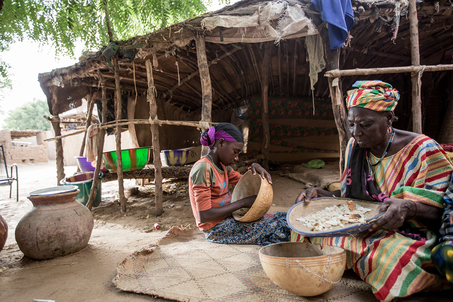 Adeoula, 12 years (RELEASED) and her grandmother prepare a meal together in their homestead, Gao Northern Mali. Adeoula and her brother were orphaned during the conflict and live with their grandmother Hadish. Ongoing conflicts in the northern regions of