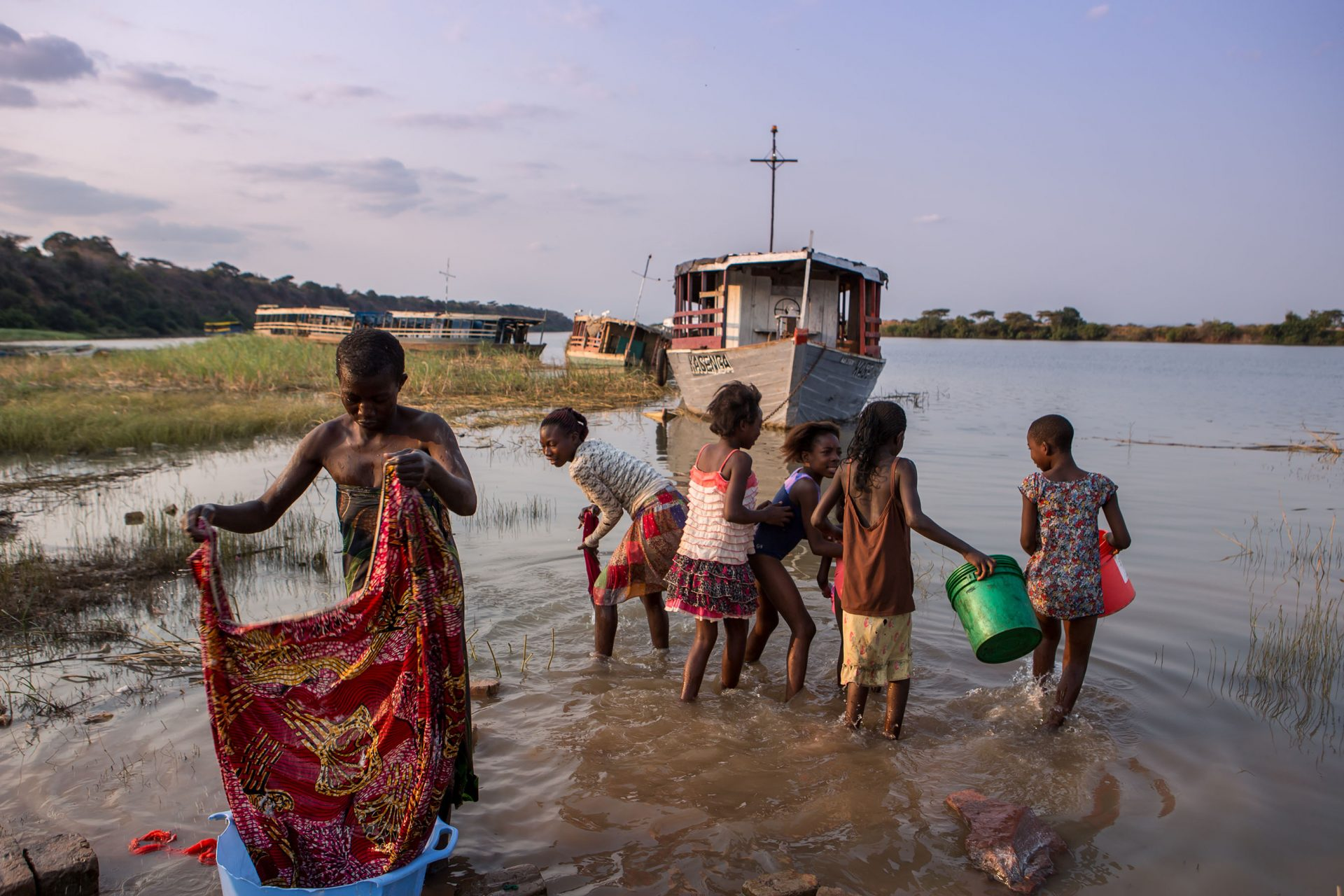 If one generation is educated and empowered regarding HIV, the next generation will make better life choices for themselves and for own children. A mother does her washing in the afternoon with her daughters along the banks of the Luapala River, Haute K