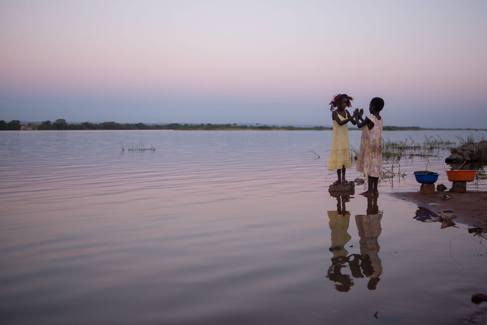 """""""Women aren't the problem, but the solution. The plight of girls is no more a tragedy than an opportunity."""" - Nicolas Kristof and Sheryl Wundunn, authors of  """"Half the Sky""""Two young girls play a game together as evening falls on the banks of t"""