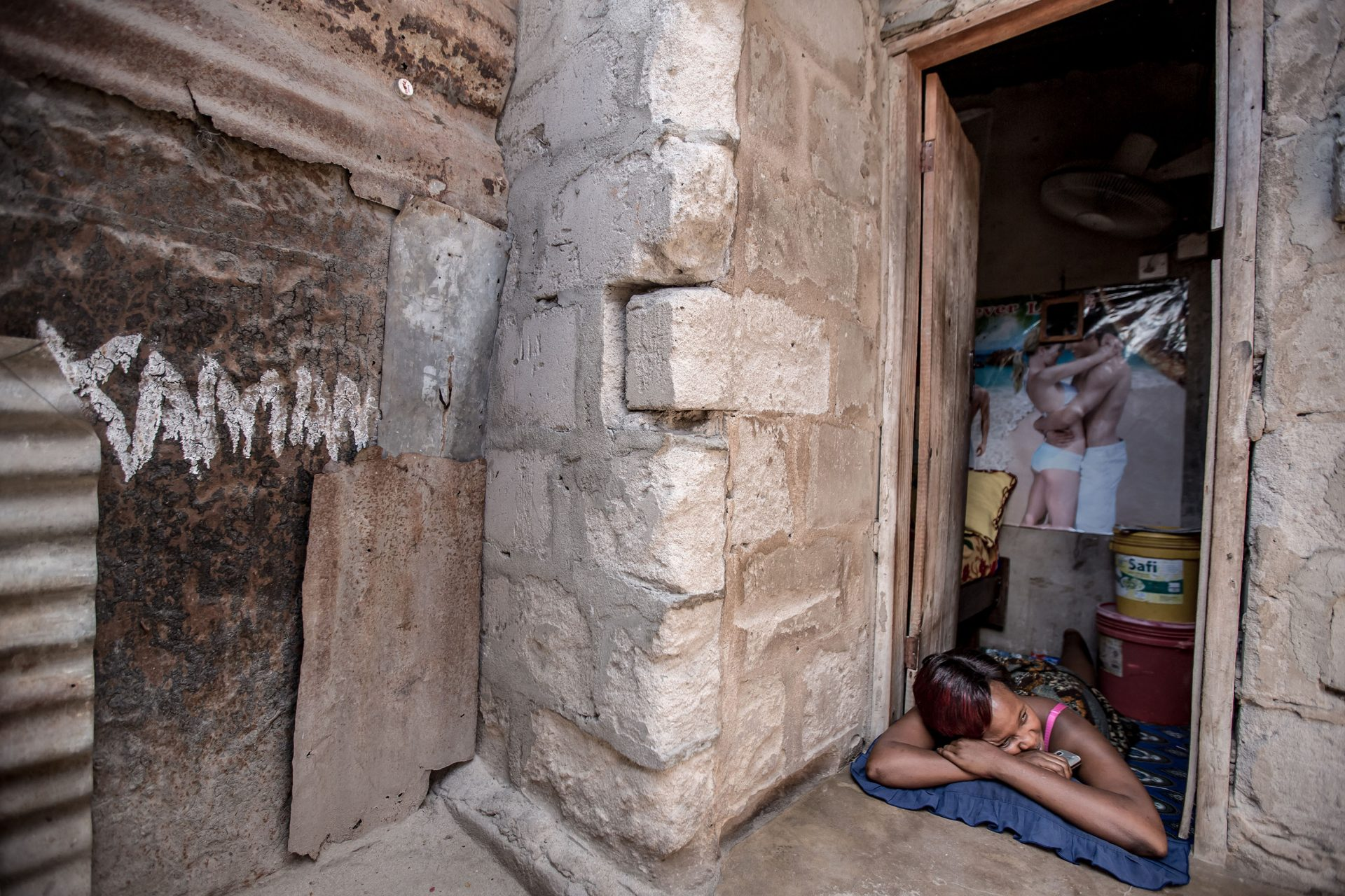 A young woman relaxes in the doorway of her bedroom. This is the same room where she accommodates her clients, as well as lives with her baby, sleeps and eats. In downtown Dar Esalaam, Tanzania, community health workers offer free HIV testing in brothel