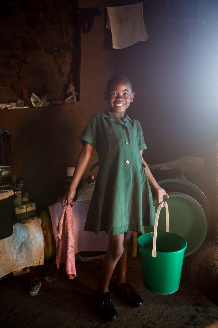 Botomelo Moahlodi (9yrs) prpeares for school, Ha Khapiso Village, Lesotho (UNICEF/Schermbrucker)