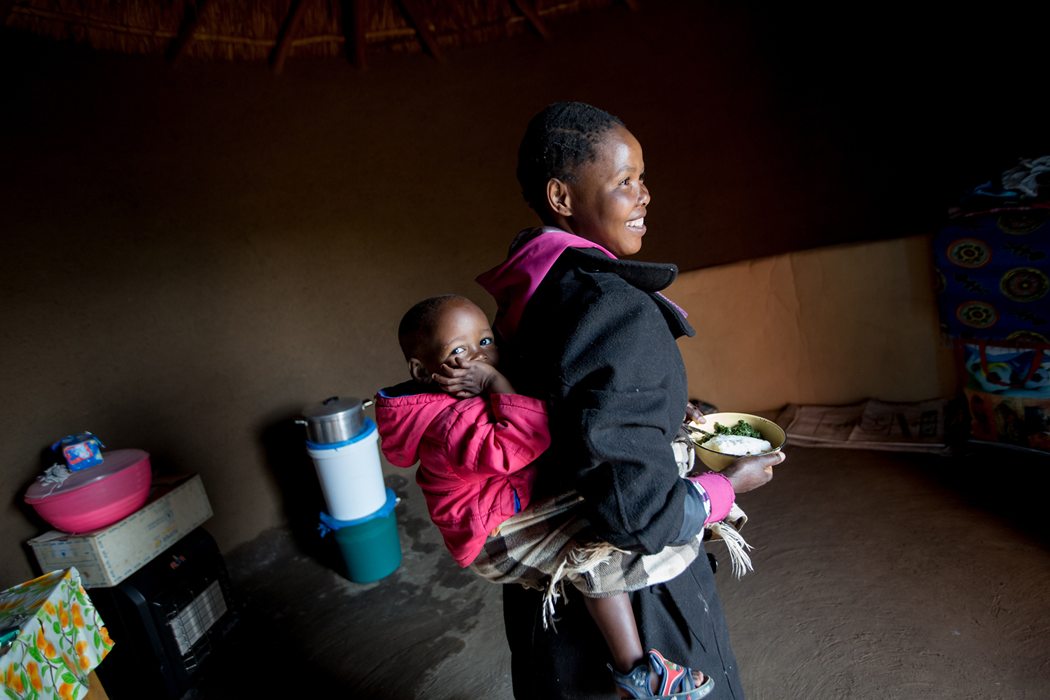 Makhatleho Moahlodi (26 yrs) and Katleho David Moahlodi (18 months) in their hut in the Ha Khapiso Village, Lesotho (UNICEF/Schermbrucker)