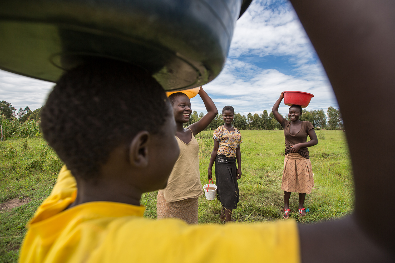 Annoline and her sisters Purity (yellow top) and Mollie go and fetch water near their home in Nyarongi, Homa Bay Kenya 14 November Schermbrucker/ACTION AID. (Annoline was encouraged by the Women's Network to return to school after giving birth when she was 14 yrs old. Tragically, she lost the baby at birth)